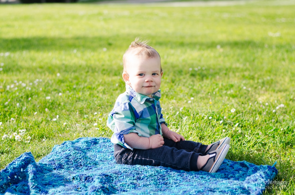 Cute little boy sitting on crochet blanket at the park - Monterey Family Portraits