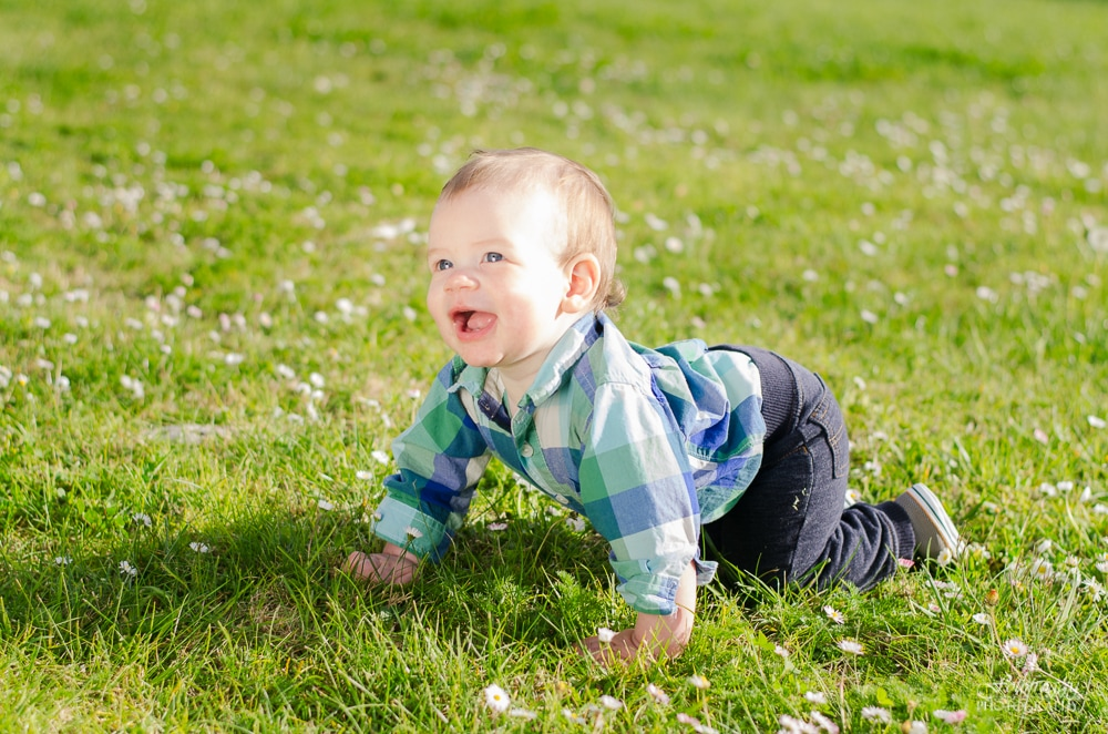 Sweet little boy with big smile crawling in the grass - Monterey Bay Family Photos