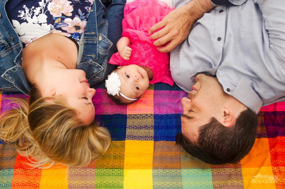 Adorable baby girl in pink laying with parents in blue on rainbow blanket.