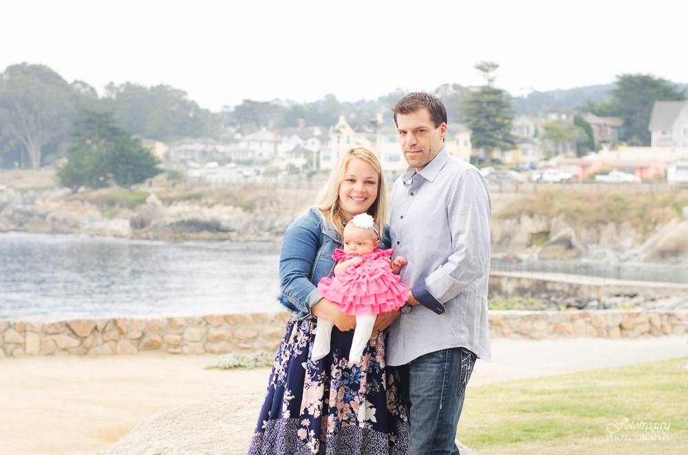 Cute couple in blue baby girl in pink ruffles at Lovers Point Pacific Grove Ca