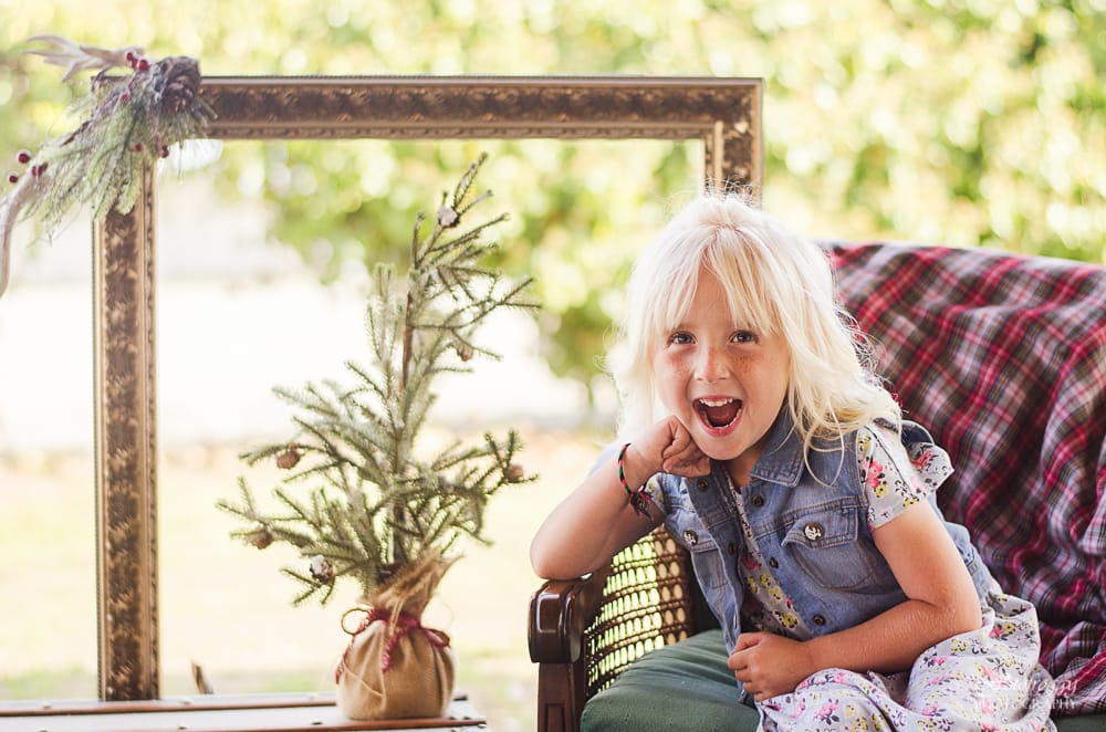 Excited little blonde girl with Holiday plant and gilded frame. www.fotofroggy.com